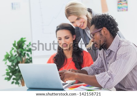 Three designers working together on a laptop in a bright office - stock photo