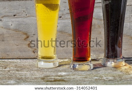 Three different beer glasses of coloured beers, amber, red and black with condensation, sitting on a rustic bar. - stock photo
