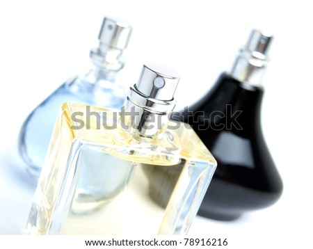 Three different bottles of perfume on a white background. - stock photo