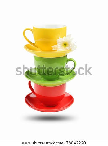 Three different colored cups facing each other on a white background