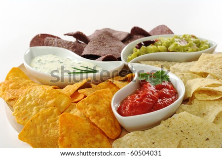 Three different dips (guacamole, tomato-chili and cream cheese dip) with salty and cheese tacos and chips made of Peruvian purple corn on white (Selective Focus) - stock photo