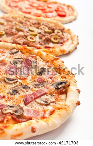 three different kinds of pizza in a row - stock photo