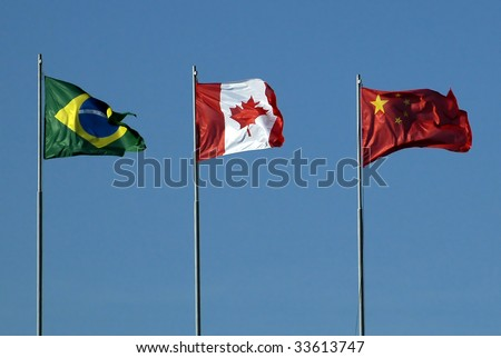 Three different national flag's on flagpole opposite blue sky