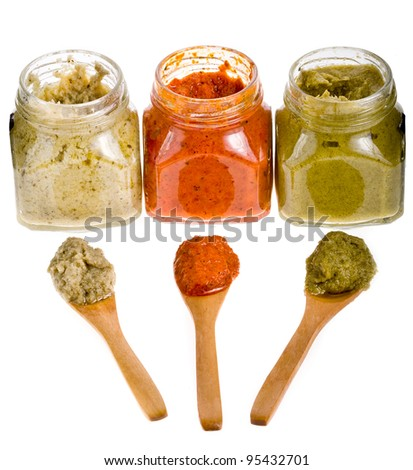 Three different sauces in glass jars with wooden spoons on white background - stock photo