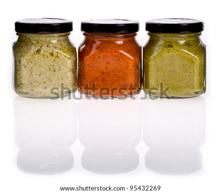 Three different sauces in jars on white background - stock photo