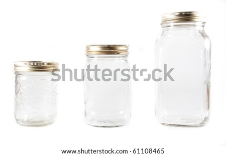 Three different sized glass mason jars for canning in line on a white isolated background.
