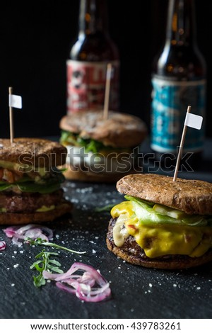 Three Different Tasty Big Burgers with Cheese, Bacon, Chicken and Sauce on Dark Stone Background, Beer and Soft Drinks on the Background, Close-up - stock photo
