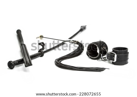 Three different types of whips and hand cuffs made of leather for sexual role-playing and s&m games.  - stock photo