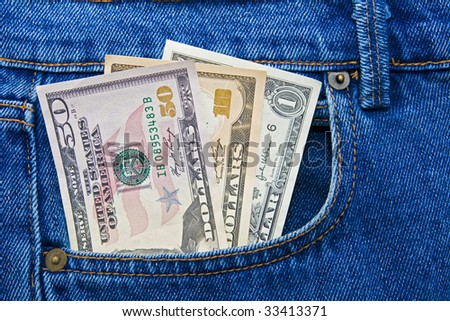Three different US currency dollar notes in the pocket of pair of blue jeans
