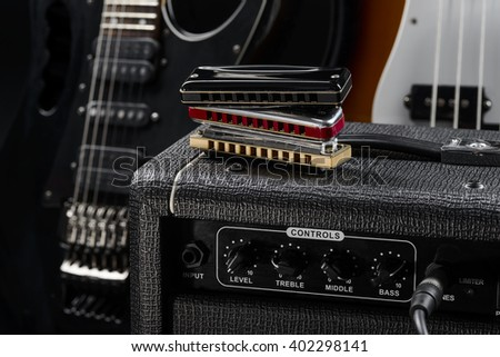 Three differently colored harmonicas on the top of guitar amp. The background is busy with two guitars (electric and bass). Glossy strings. - stock photo