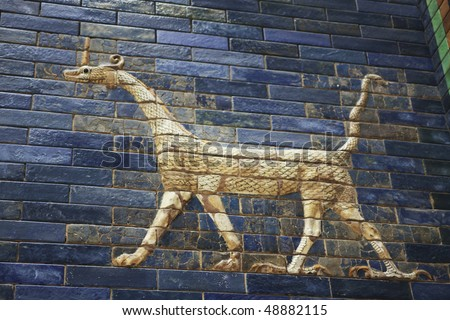 Three dimensional tiled dragon from the Babylonic Ishtar Gate. Dedicated to the Babylonian goddess Ishtar, the Gate was constructed of blue glazed tiles with dragons and aurochs. - stock photo