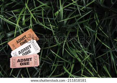 Three discarded carnival tickets isolated on green grass background lower left corner leaving room for text - stock photo