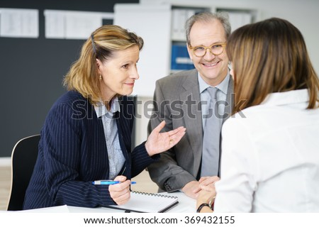Three diverse business colleagues sitting round an office table having an animated discussion with focus to an attractive middle aged woman - stock photo