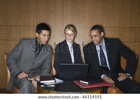 Three diverse businesspeople sit at a small table and look at a laptop together. Horizontal format. - stock photo