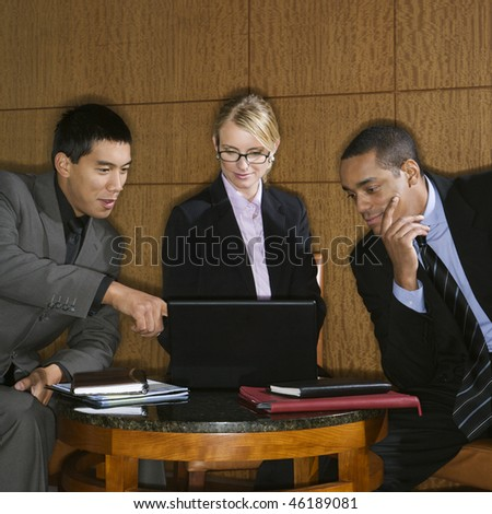 Three diverse businesspeople sit at a small table and look at a laptop together. Square format. - stock photo
