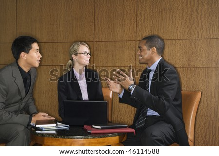 Three diverse businesspeople sit at a small table with a laptop and talk together. Horizontal format. - stock photo