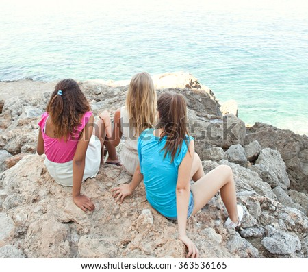 Three diverse friends, caucasian and african american teenager girls together on rocks, relaxing and contemplating the blue sea, outdoors nature. Healthy well being holiday travel lifestyle, beach. - stock photo