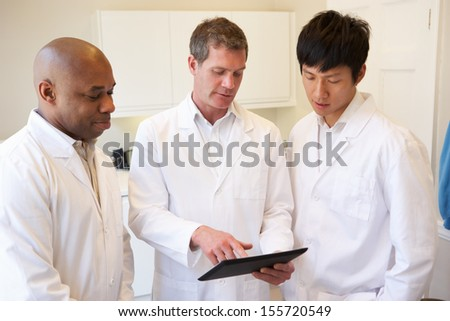 Three Doctors Having Discussion Using Digital Tablet