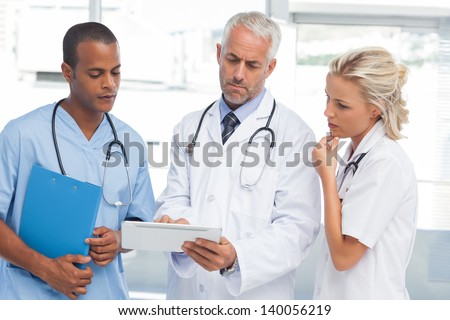 Three doctors using a tablet in a bright office - stock photo