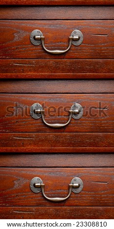 Three drawer dresser. Close up detail of handles and wood grain finish. - stock photo
