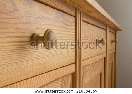Three drawers of a chest of drawers with knobs, soft wood, tidiness - stock photo