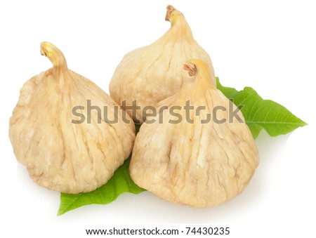 three dried figs on the green leaves - stock photo
