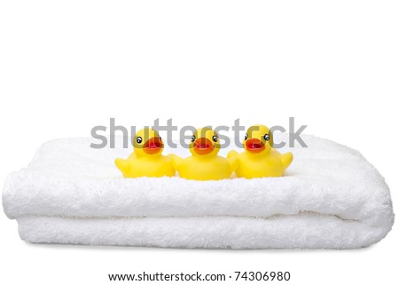 Three ducks in a row.  Three yellow rubber ducks sat on a fluffy white towel isolated against a white background with copy space - stock photo