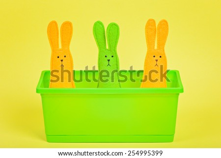 Three easter Bunnies in flower pot on yellow paper background - stock photo