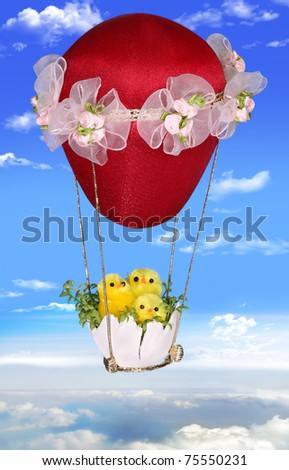 Three Easter chickens on a balloon soaring in the sky. Background for an Easter card with a place for your text. Handiwork.