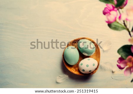 Three  easter eggs in a wooden bowl on a light background. Vintage - stock photo