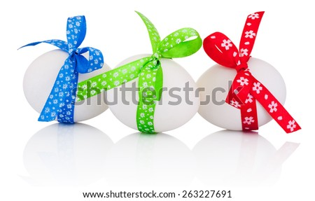 Three Easter eggs with festive bow isolated on white background - stock photo