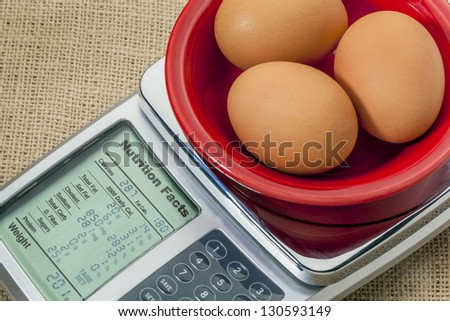 three eggs on diet scale displaying nutrition facts - a diet concept