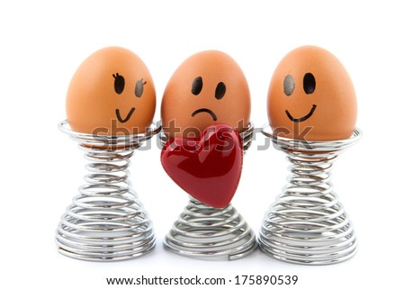three eggs with facial expressions in egg holder and heart symbol - stock photo