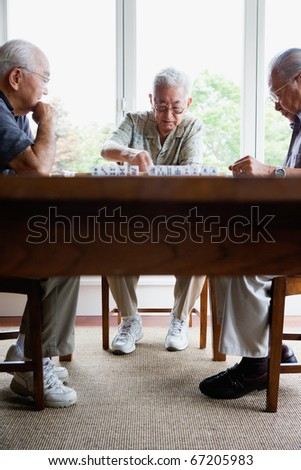 Three elderly men sitting at table playing game - stock photo