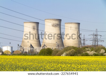 Three electricity power station towers viewed across a field of rapeseed flowers - stock photo