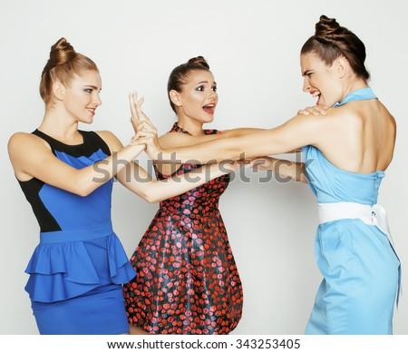 three elegant fashion woman fighting on white background, bright dresses evil faces - stock photo