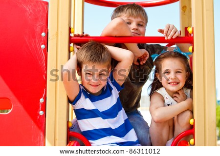 Three elementary aged children in the playground - stock photo