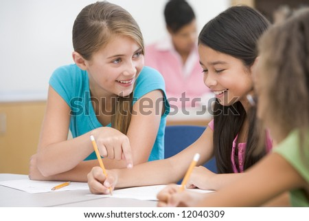 Three elementary school pupils talking in classroom - stock photo