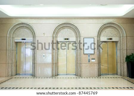 Three elevator doors in corridor of office building - stock photo