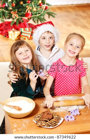 Three embracing kids busy with Christmas cooking - stock photo
