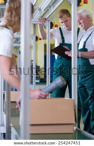 Three employees working on production hall - stock photo