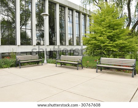 three empty benches on a concrete patio by a glass building - stock photo