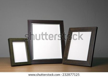 Three empty(blank) wood photo frames(walnut) on the wood table(desk) at the studio. - stock photo