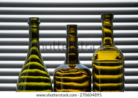 three empty bottles of wine on the background of blinds backlit - stock photo