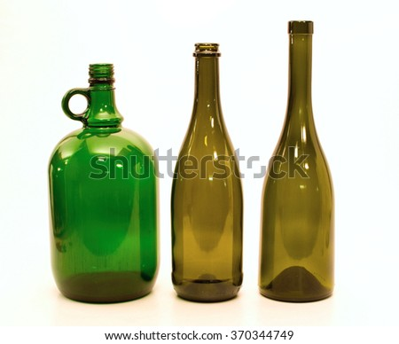 Three empty glass bottles of different shapes