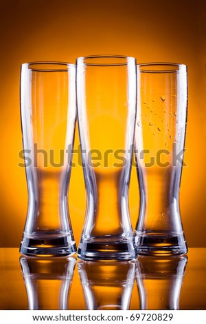 Three empty glass glasses for beer or drinks on a yellow background - stock photo