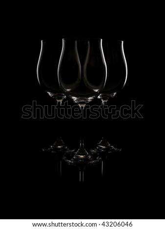 Three empty glasses, a dark background. - stock photo
