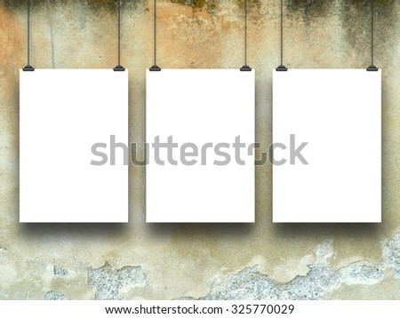 Three empty paper sheet frames on grungy wall background - stock photo