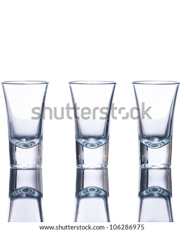 Three empty shot glasses on a reflective surface. Isolated on white. - stock photo