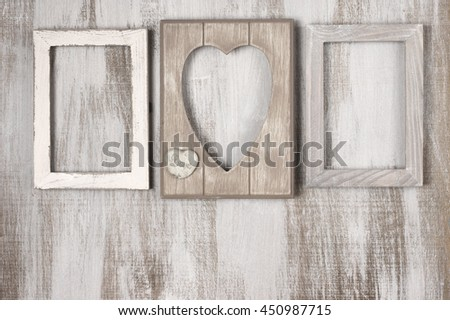 Three empty vintage wooden photo frames on rustic wood background. Top view point.